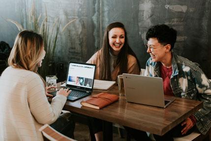 Three people smiling around desk